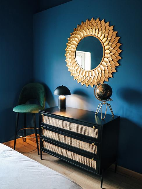 chambre avec mur bleu, miroir doré, et commode noire avec du cannage chez Julien Duquaire