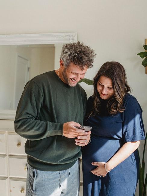 couple homme et femme en train de regarder le téléphone portable, la femme est enceinte