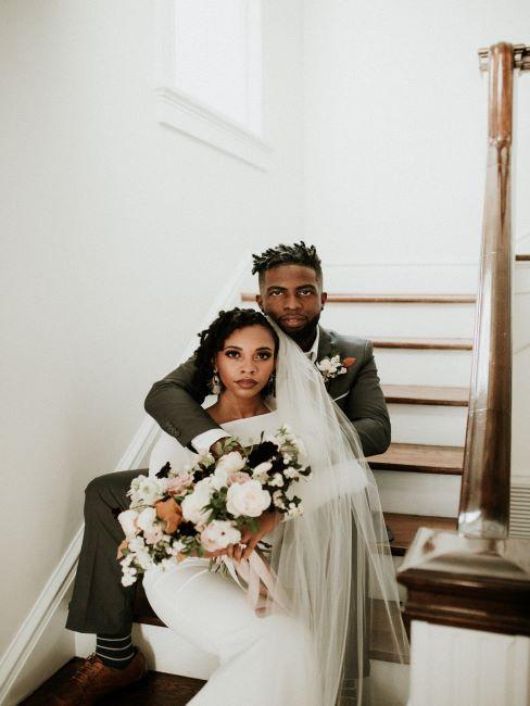 couple de mariés assis dans l'escalier, belle robe de mariée, bouquet de mariage, mariage traditionnel