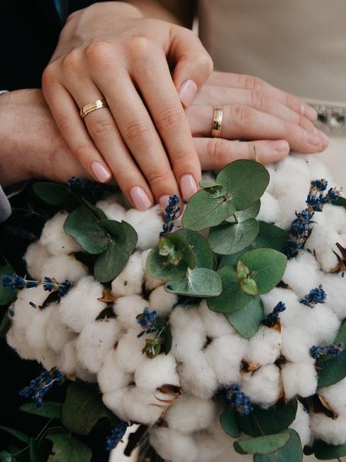 mains couple marié posées l'une sur l'autre, les alliances en évidence, bouquet en fleurs de coton