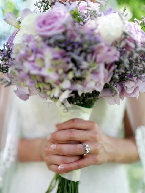 mains d'une mariée enlaçant un bouquet de fleurs