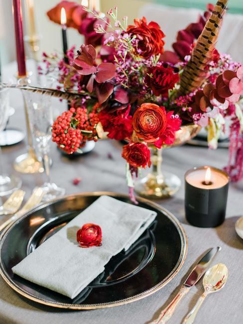 décoration de table avec assiettes noires, couverts dorés et bouquet de fleurs rouges