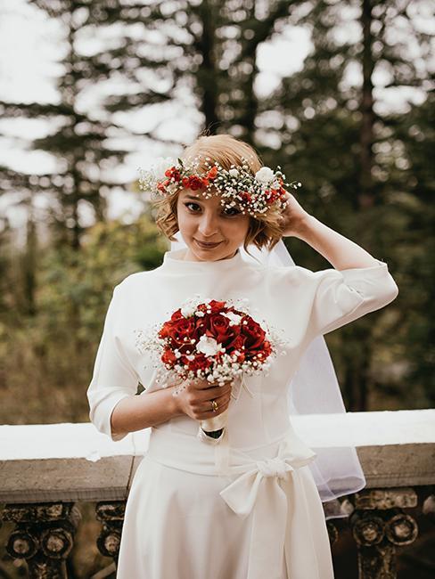 mariée habillée avec une robe longue et une courronne de fleurs rouges et blanches idéale pour un mariage en hiver