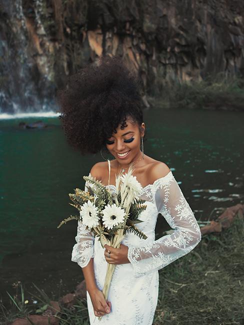 mariée habillée avec une robe à manches longues en dentelle