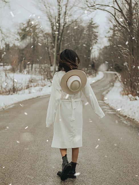 femme portant un manteau blanc et un chapeau beige en hiver