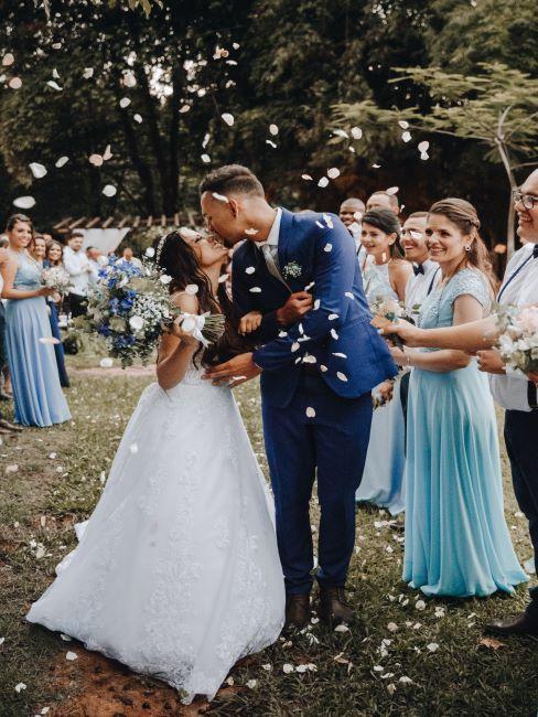 les mariés en train de s'embrasser entourés des convives, mariage à l'extérieur
