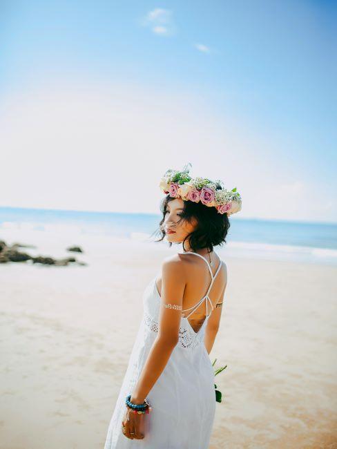 la mariée en couronne de fleurs sur la tête pose à la plage