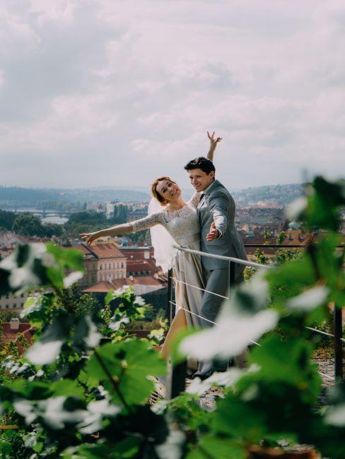 un couple de jeunes mariés sur un balcon, avec une belle vue sur une ville et les montagnes à l'horizon