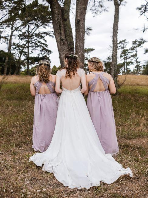 la mariée avec ses demoiselles d'honneur pose tournée de dos, dans le bois