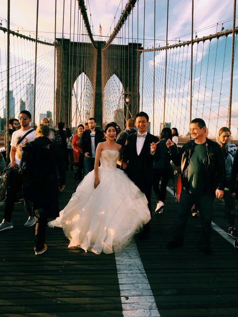 couple ed mariés pose sur le pont londonien, entouré de touristes