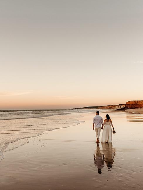 deux mariés entrain de marche sur une plage