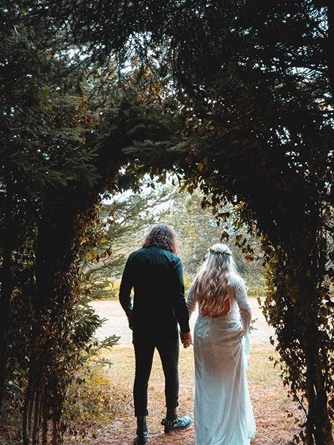 deux mariés entrain de marcher sous une arche végétale