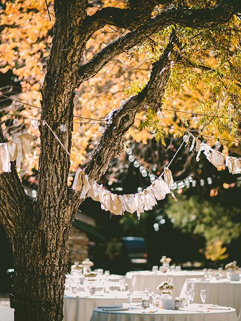 mariage dans un jardin avec table blanche et guirlandes accrochées aux arbres