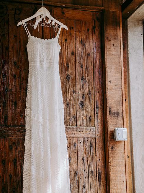 robe de mariée accrochée dans une grange