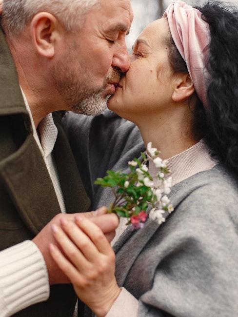 couple des gens mûrs en train de s'embrasser, il lui tend un petit bouquet de fleurs
