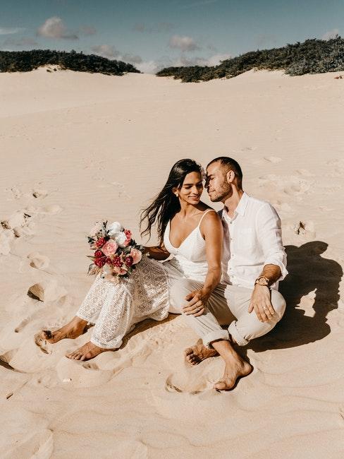 couple de mariés assis sur une plage dans le sable