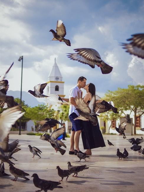 couple d'amoureux enlacés debout sur une place du marché, les oiseaux s'envolant autour