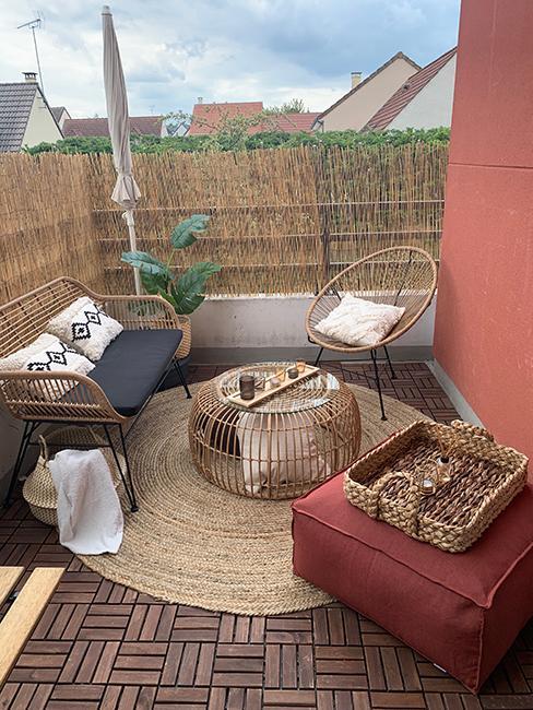 après aménagement d'un balcon style boho avec ensemble de jardin en rotin avec table ronde, petit canapé de jardin et pouf rouge chez veronica sither