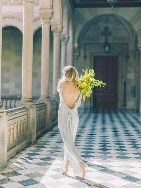 mariée avec bouquet de fleurs dans un couloir de château