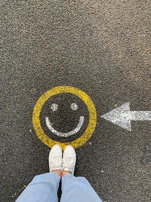 jambe avec un smiley dessiné à la craie sur du goudron