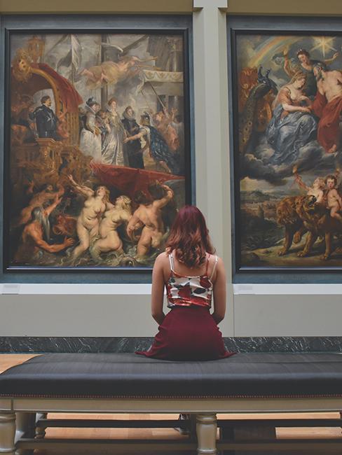 personne entrain de regarder des tableaux au musée du louvre
