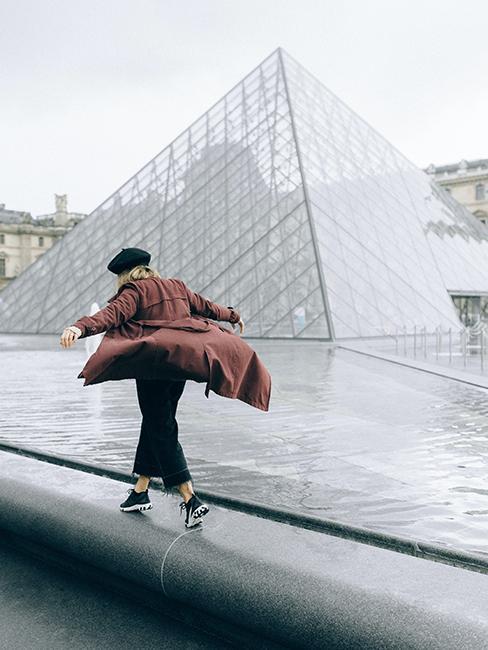 personne entrain de marcher sur le rebord de la fontaine de la pyramide du louvre