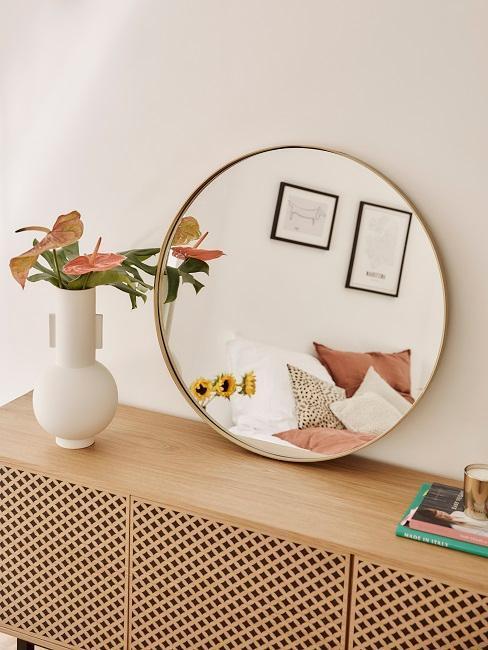 miroir rond sur commode en bois clair et fleurs en vase