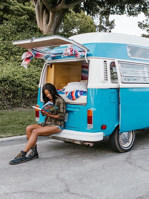 personne entrain de lire à coté d'un van bleu