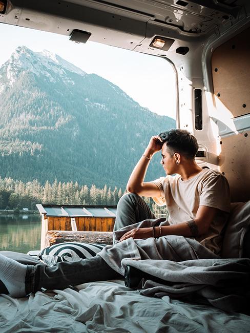 personne dans un van aménagé regardant les montagnes