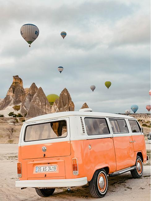 van vintage orange dans le desert avec des montgolfières