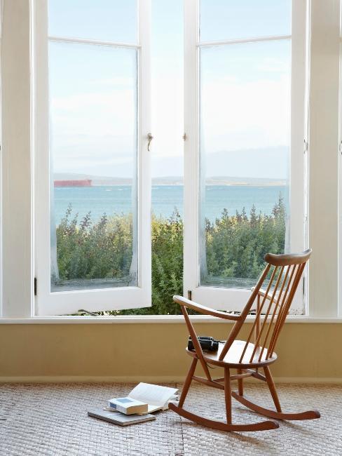 grande fenêtre blanche et fauteuil en bois