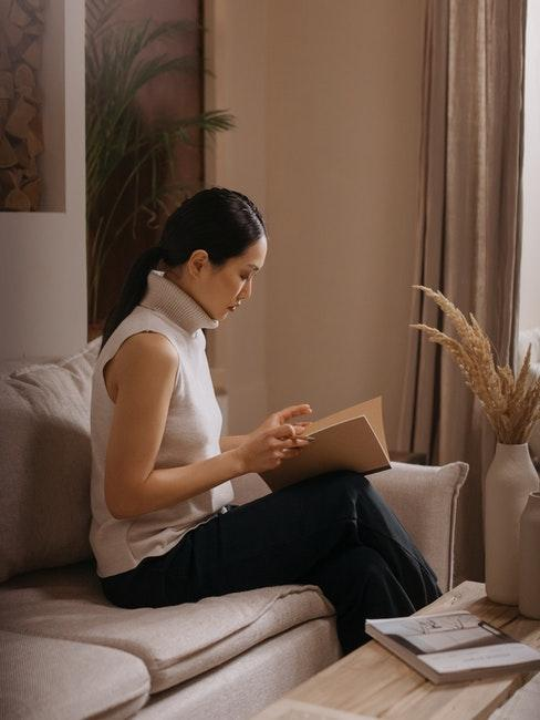 femme qui lit sur un canapé scandi