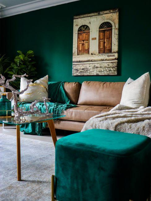 salon aux murs vert émeraude, canapé en cuir, plaid vert, pouf en velours vert émeraude