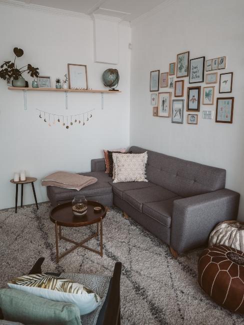 petit salon avec décoration boho, cadres photos, étagère murale, canapé gris et tapis berbère