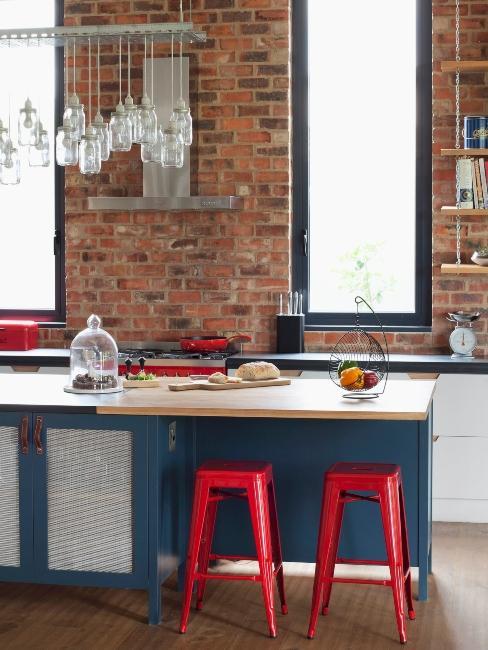 cuisine loft avec mur en brique et tabourets rouges