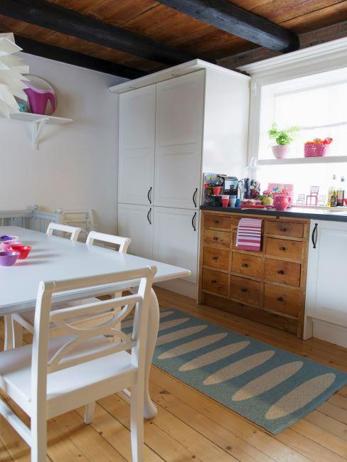 cuisine blanche avec petits détails roses et boisés, tapis de cuisine, sol en bois