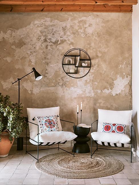 salon avec deux fauteuils blancs et mur brut