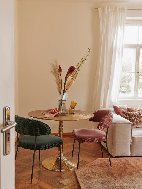 salle à manger/salon avec table ronde et une chaise rose et une chaise verte