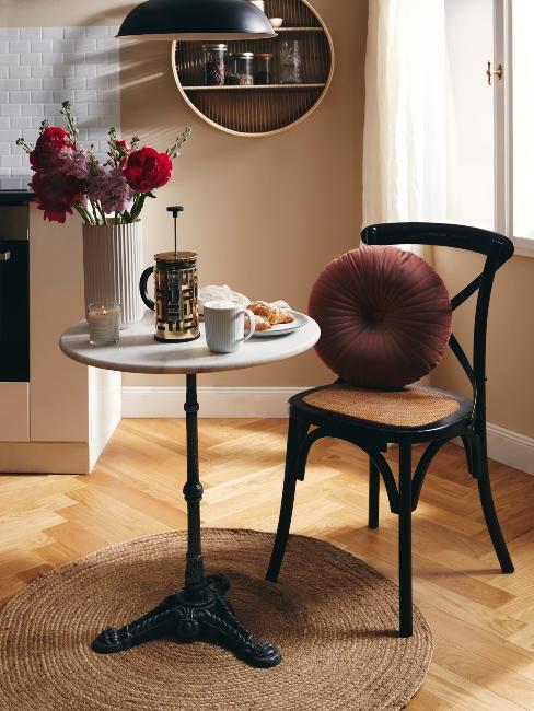 petite table ronde en marbre avec chaise rustique et coussin vieux rose