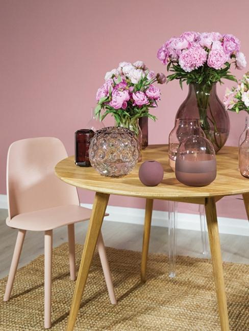 table ronde en bois scandi, chaise en plastique et vases en verre teinté