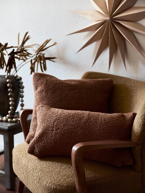 étoile en bois au mur au-dessus d'un fauteuil marron