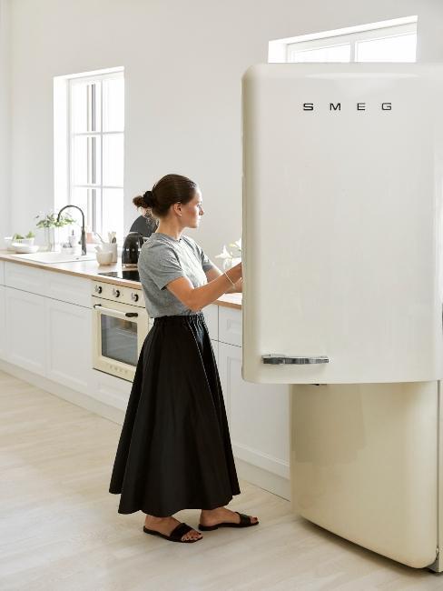 femme nettoyant un frigo crème de style rétro dans une cuisine contemporaine