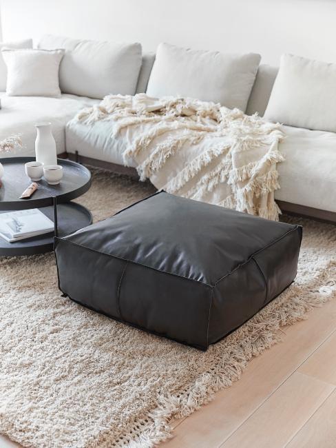 salon moderne avec canapé blanc et pouf en cuir foncé
