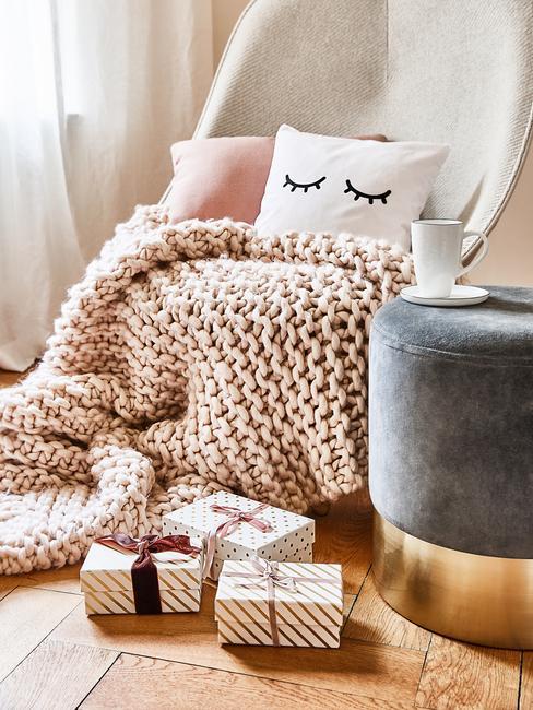 piece parquet avec fauteuil plaid rose pouf gris coussins et cadeaux sur le sol