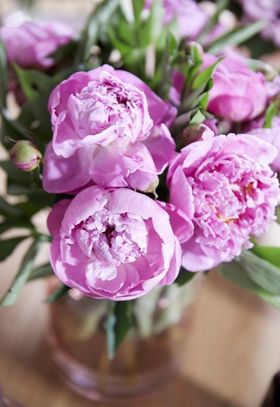 bouquet de fleurs roses dans un vase posé sur une table