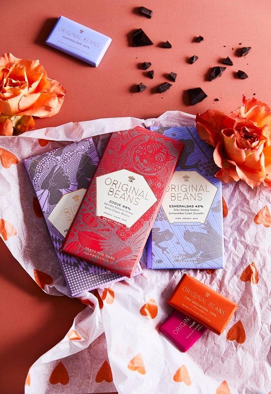 tablettes de chocolat rouge, bleue et violette entourées de pétales de fleurs