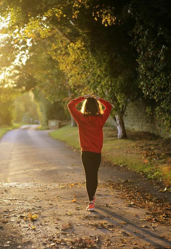 femme au pull rouge qui marche dans la forêt
