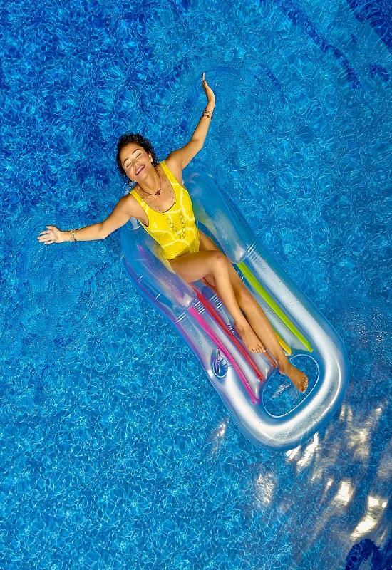 femme au maillot de bain jaune sur une bouée dans une piscine