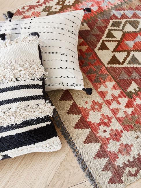 tappeto con fantasia etnica e cuscini bianchi e neri