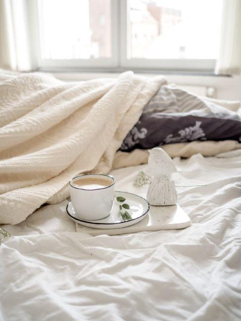 camera da letto con letto sfatto e caffè